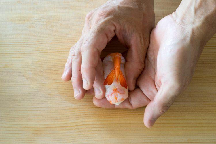 寿司職人がエビの握り寿司を作っている写真